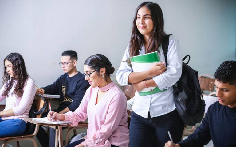 Smiling student holding textbook in classroom