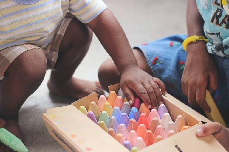 Children choosing crayons from a box