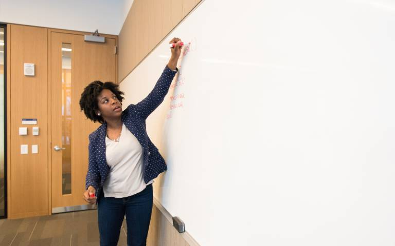 Teacher writing on a whiteboard. Image: Christina Morillo via Pexels