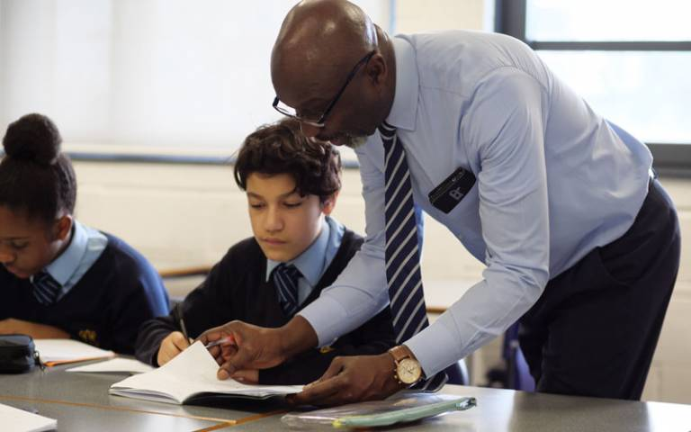 Teacher checking pupil's work in class