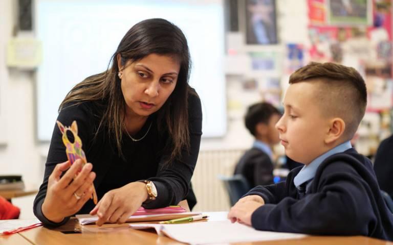 Teacher speaking to pupil in class