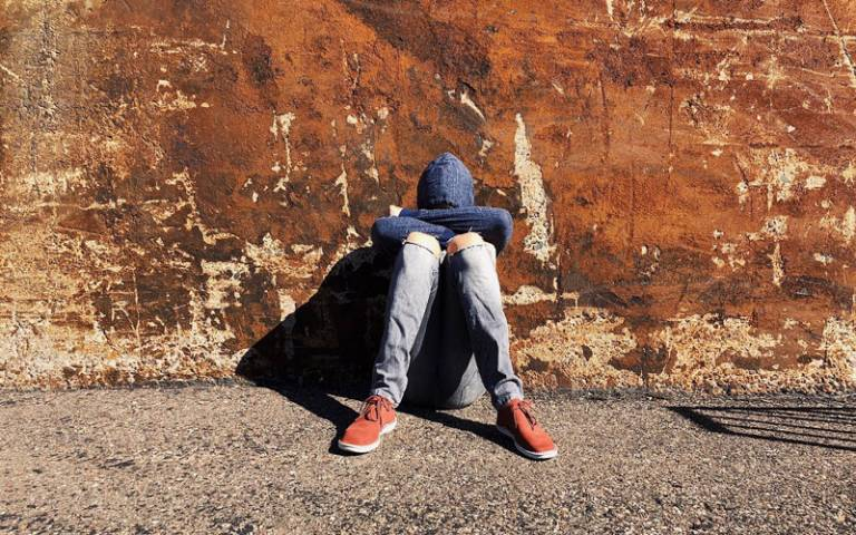 Teenage boy sat alone with his face covered and back to the wall. Image: Wokandapix via Pixabay