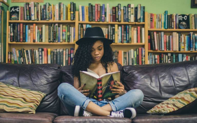 Teenager reading a book on a sofa