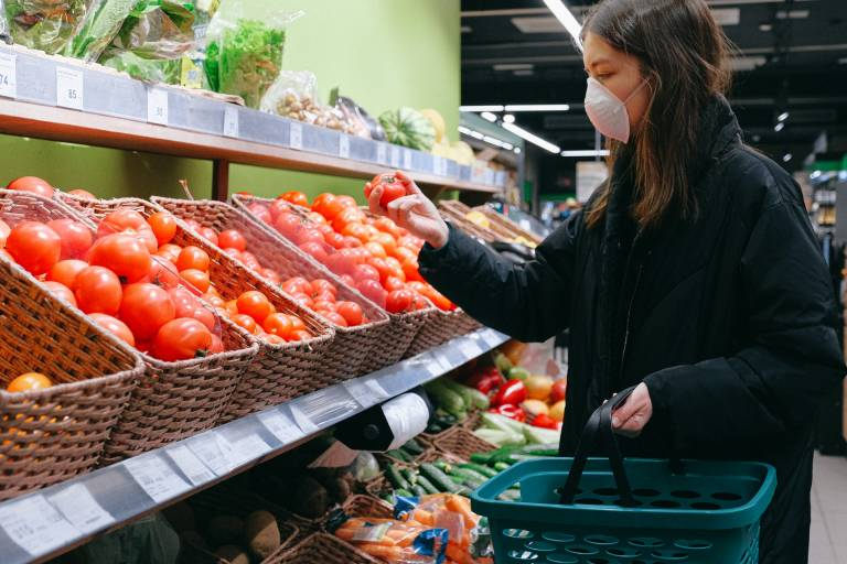 Woman wearing face mask shopping for tomatoes in supermarket. Image: Anna Shvets from Pexels