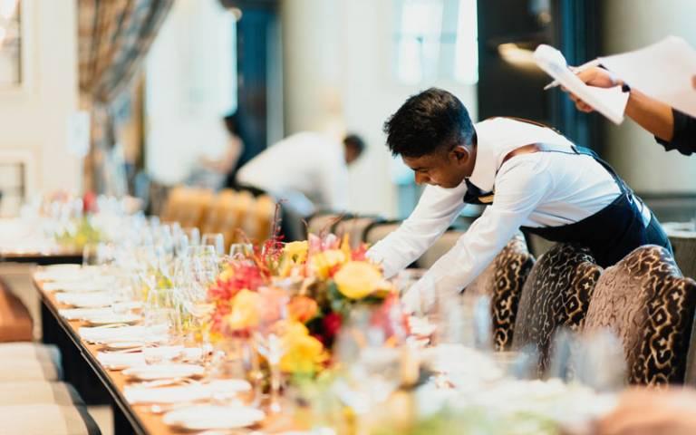 Waiter preparing dinner table. Image: chuttersnap on Unsplash