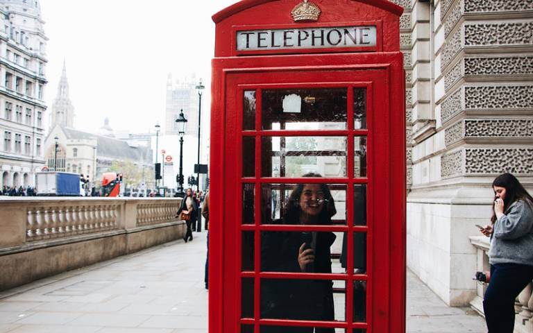 Woman in red London telephone box