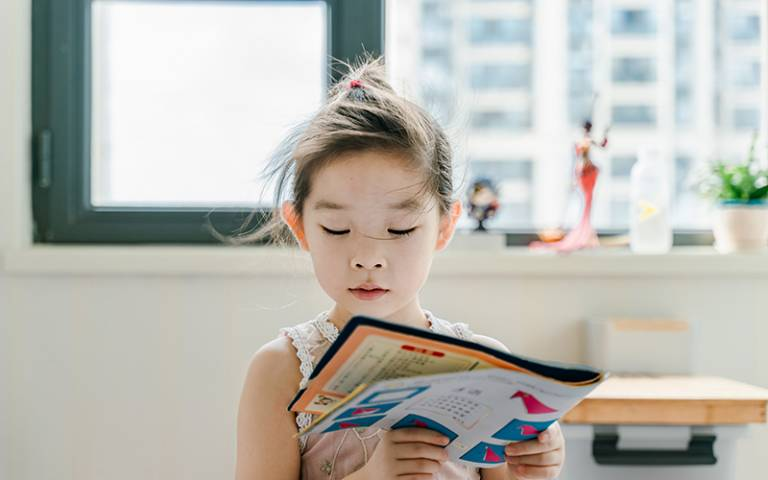Girl reading book. Image: Jerry Wang via Unsplash