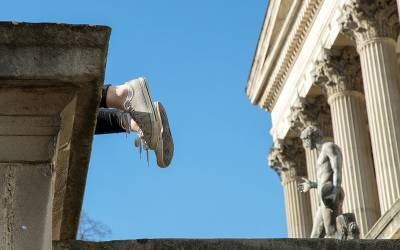 Student's feet wearing white Converse trainers hang over the edge of the UCL Portico