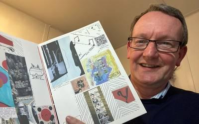 Professor John Potter holding a copy of a zine