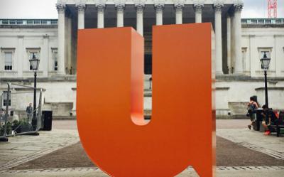 Orange three-dimensional U shape stands in the UCL Quad