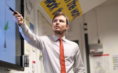 Teacher pointing to board in classroom. Image: Phil Meech for UCL Institute of Education