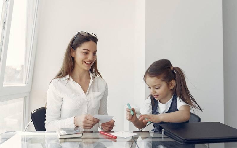 Child with parent at desk. Image: Gustavo Fring via Pexels