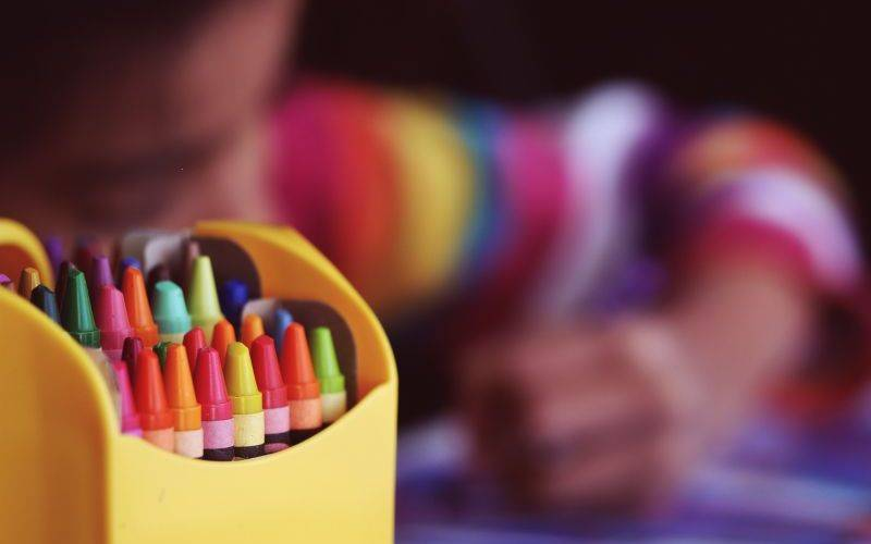 Crayons beside a child colouring. Image: Aaron Burden via Unsplash
