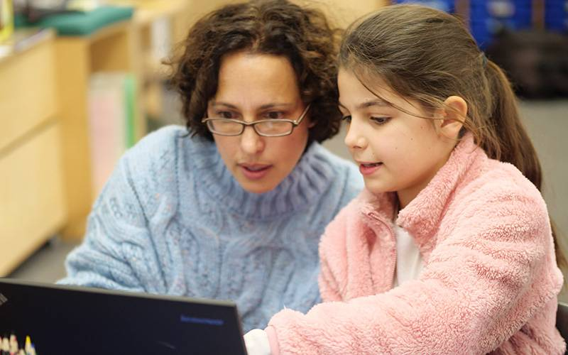 Teacher and primary pupil looking at laptop. Image: Phil Meech for UCL Institute of Education