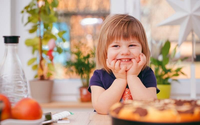 A toddler smiling. Image: Alexander Dummer via Pexels