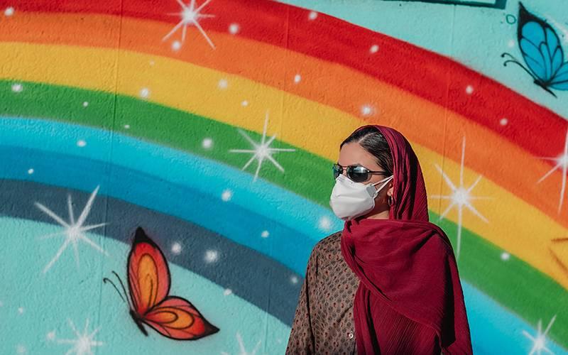 Woman standing in front of rainbow painting on wall. Image: Ashkan Forouzani via Unsplash