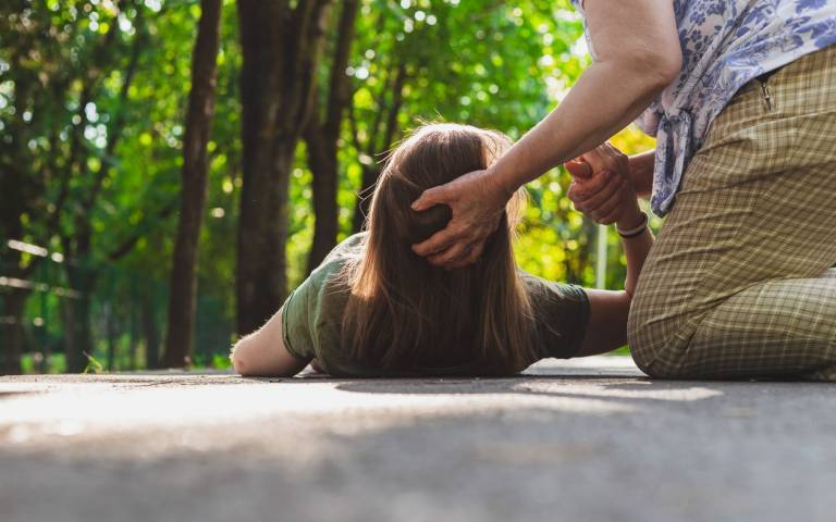 woman fainting on the ground with head supported