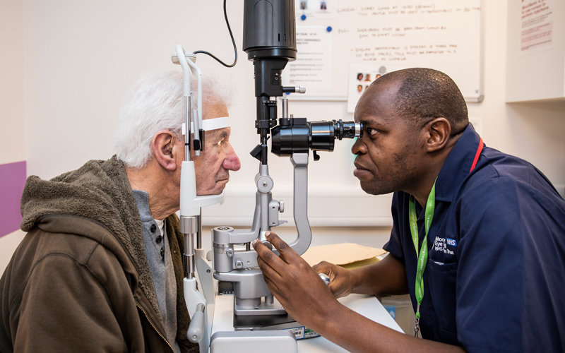 A male ophthalmic nurse examines a patient