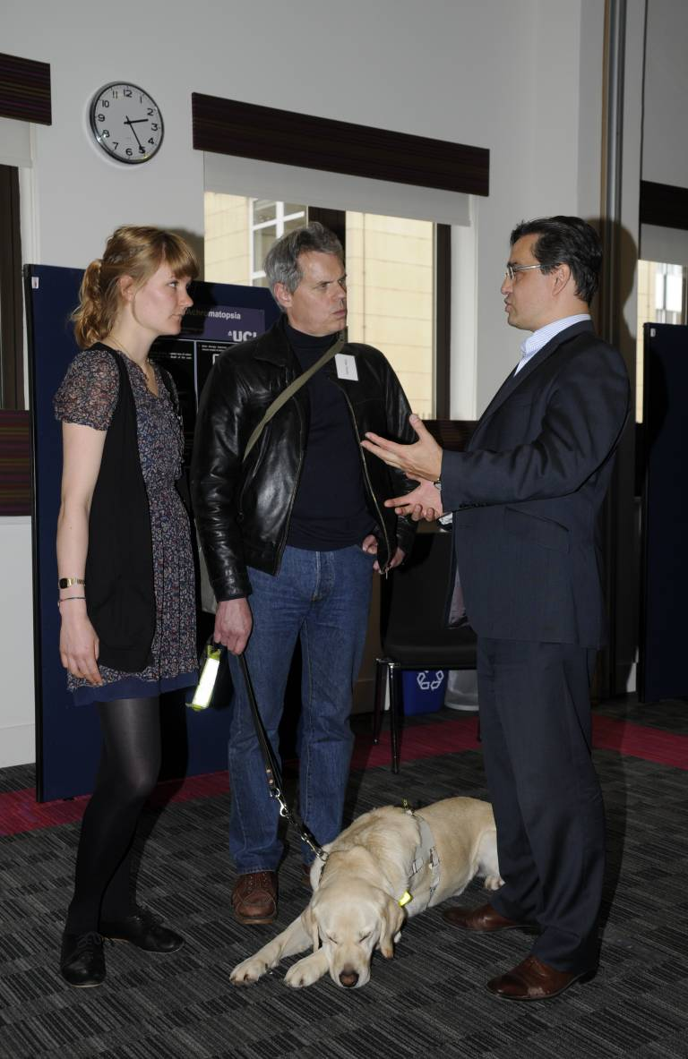 Prof Robin Ali and PhD student Sofia kline-Holthaus talking to a man with a guide dog