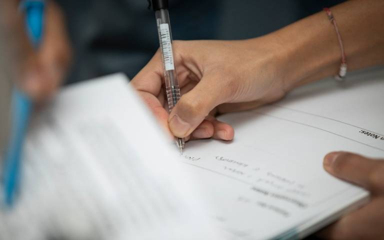Close-up of person taking notes