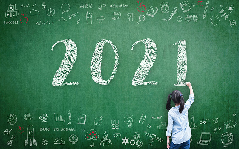 A child drawing a large 2021 on a blackboard