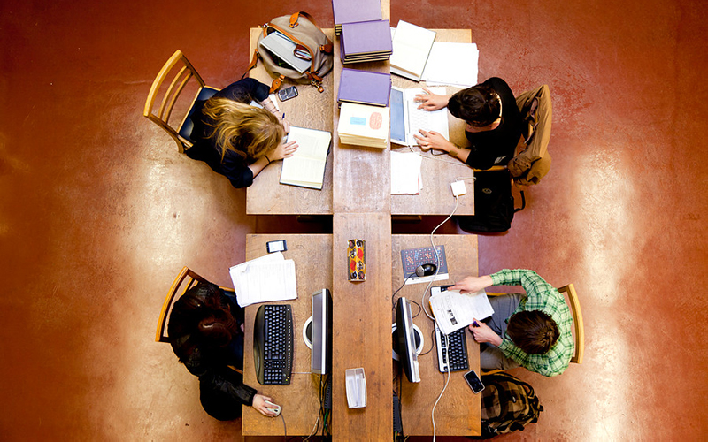 Birdseye view of four students working at desks