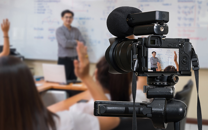 A lecturer being filmed by a camera on a tripod