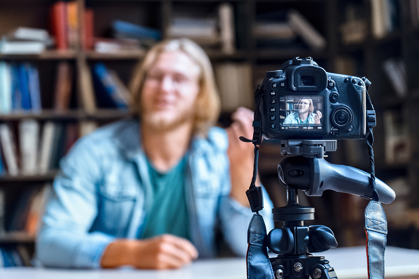 Image of a lecturer sat in front of a bookcase being filmed using a DSLR camera