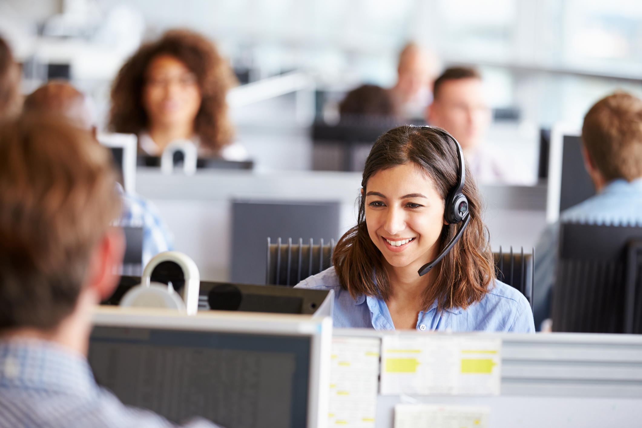 Woman on headset in office surrounded by colleagues