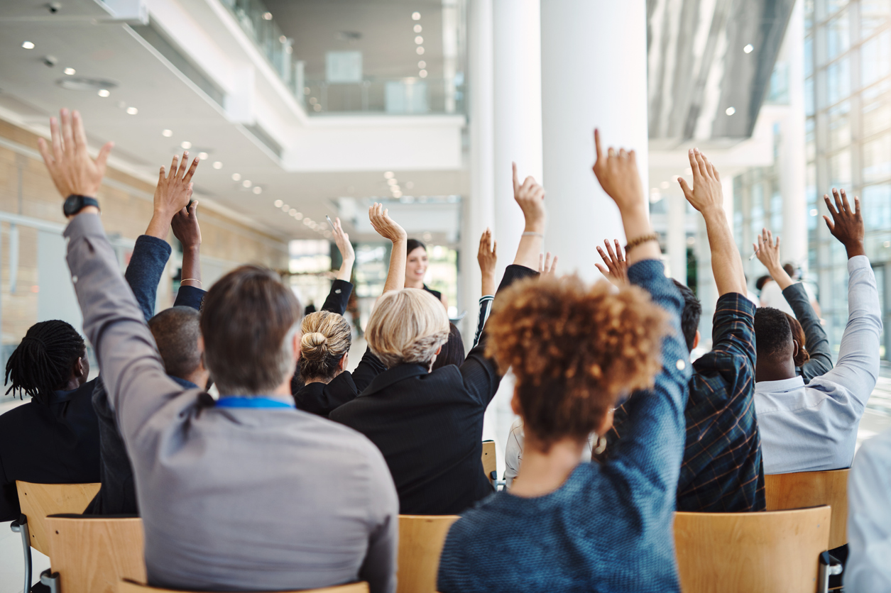 Rearview shot of a group of businesspeople raising their hands to ask questions