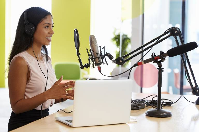 Image of Young mixed race woman recording a podcast in a studio