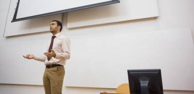 Lecturer standing against projection screen in lecture hall…