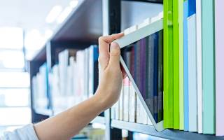 A shelf of library books and an iPad