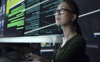 A woman looking at an overlay of computer code