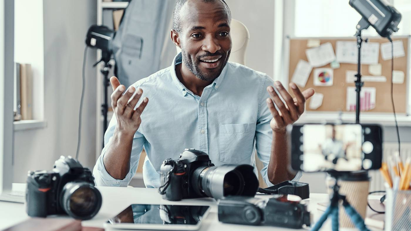 Charming young African man in shirt showing digital camera and telling something while making a video