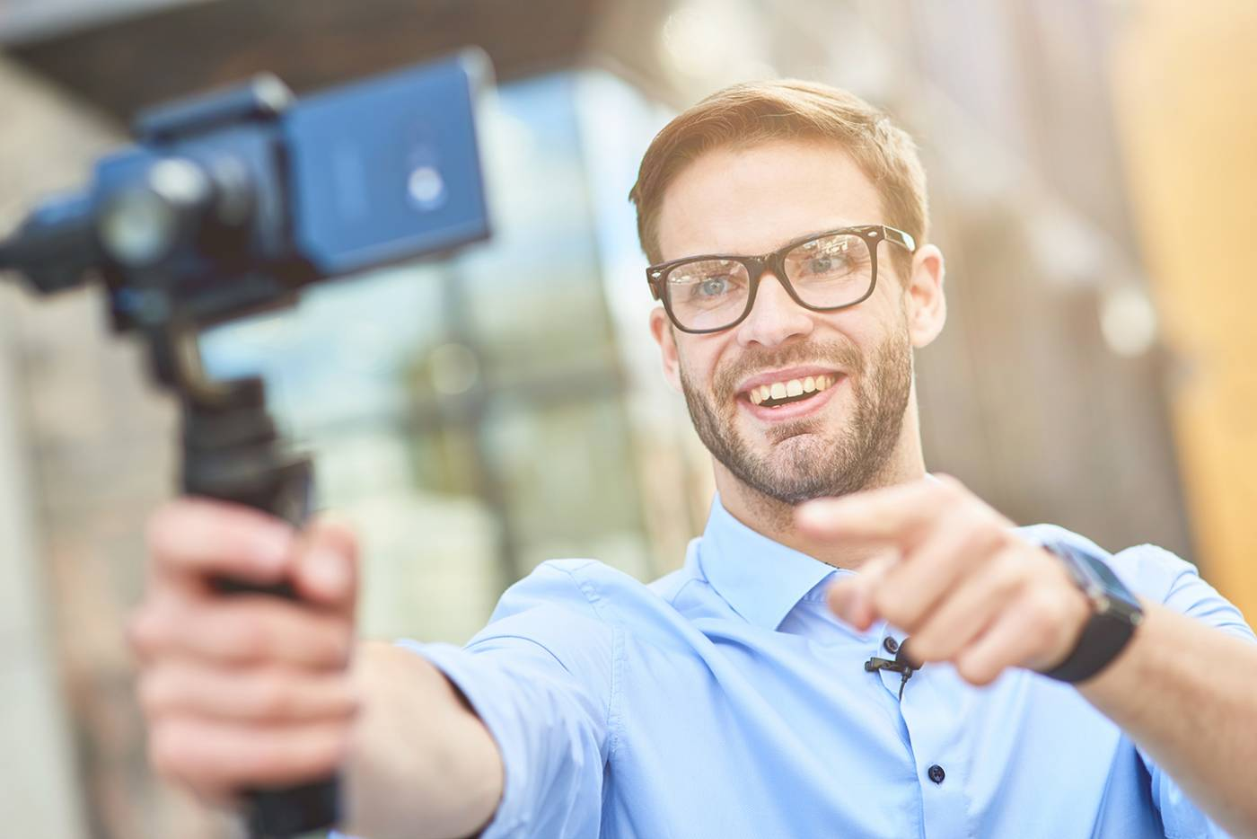 Image of man holding a gimbal with a smartphone filming himself