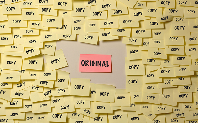 A post-it note with the word 'original' on it, surrounded by dozens of post-it notes with the word 'copy' written on them