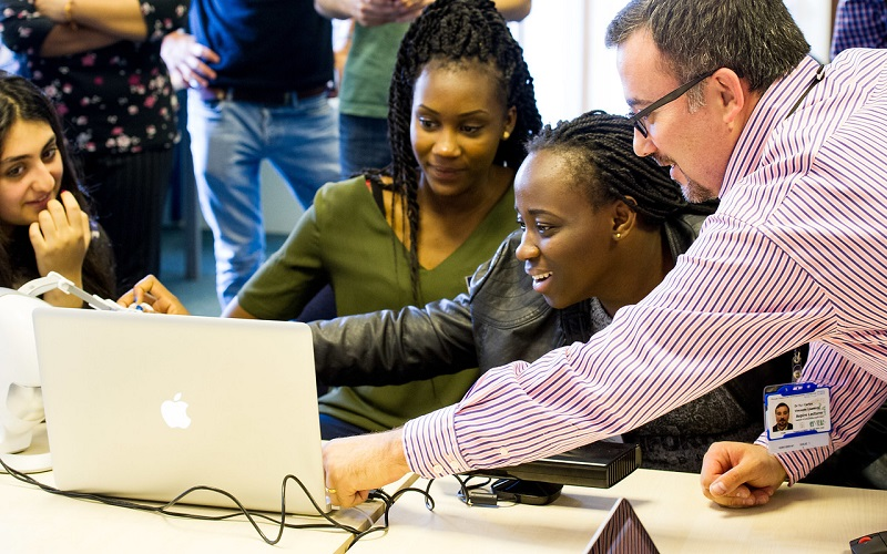 Picture of two students and lecturer around a laptop