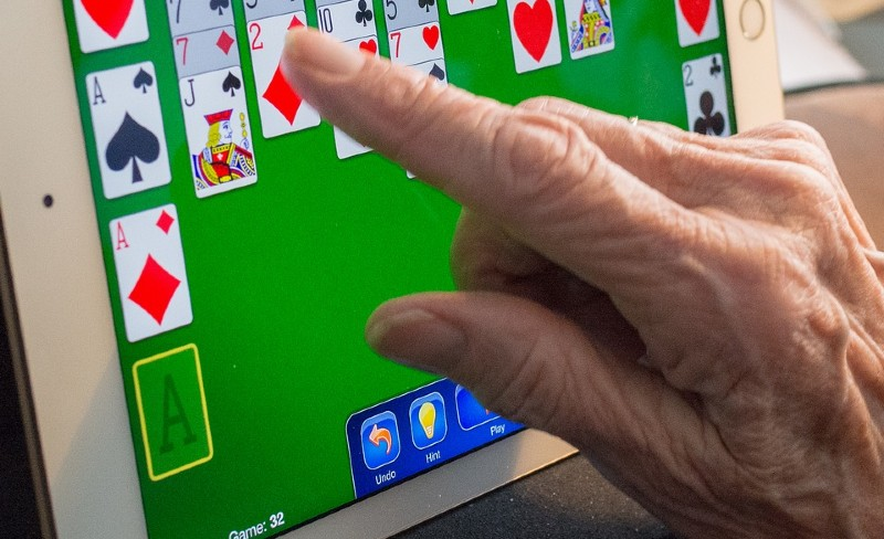 elderly person playing cards on electronic device