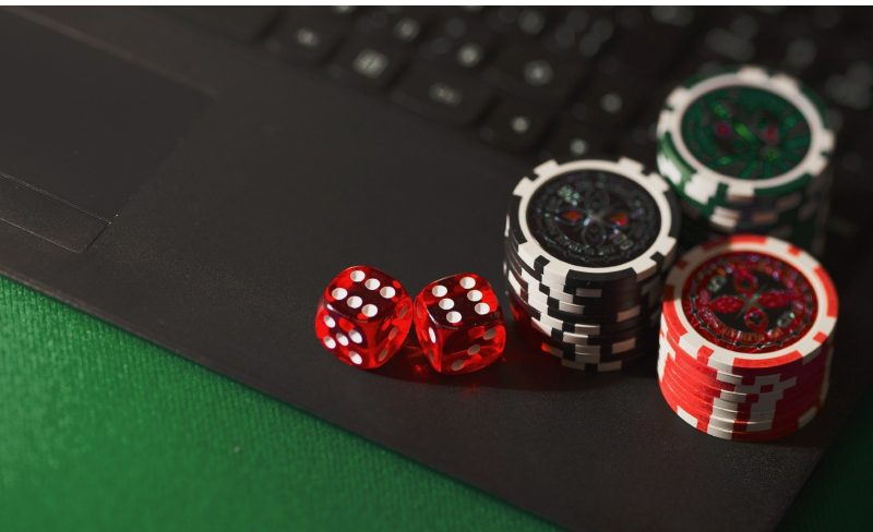 Laptop on a green table cloth with gambling chips on top of it