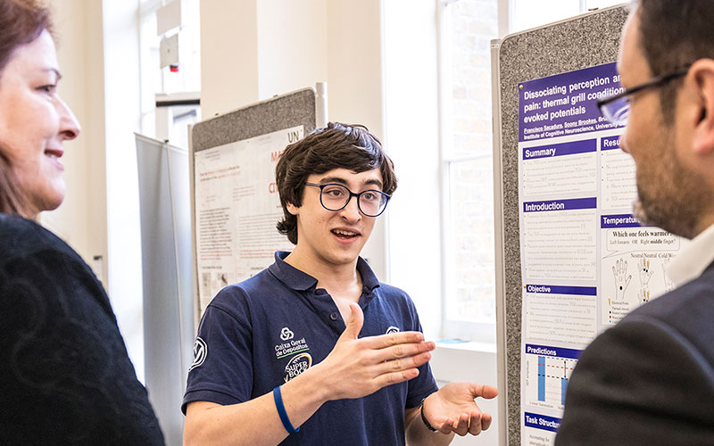 A student standing in front of his research poster, talking