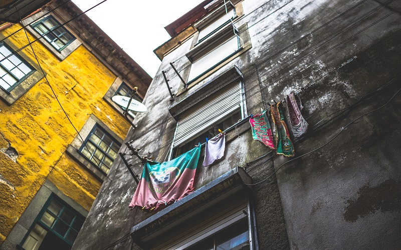Portuguese evening course - Portuguese flag hanging from a window in Porto