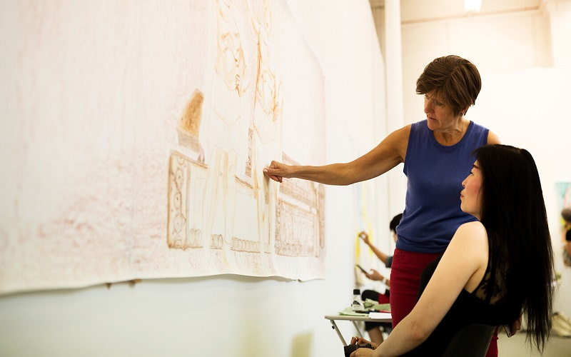Student and teacher discussing artwork in studio