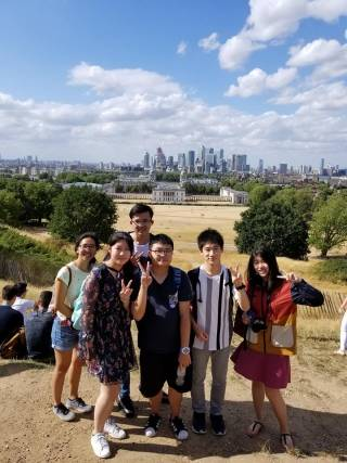 Mitsuru on a Pre-University social activity to Greenwich, posing with other students and a chaperone with the London Skyline in the background