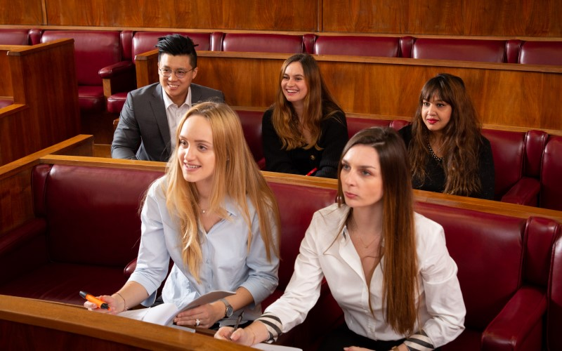 Five UCL Laws students sitting in rows at the Moot Court