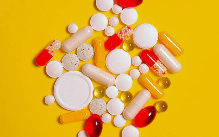 Pills of multiple colours and sizes on an orange background