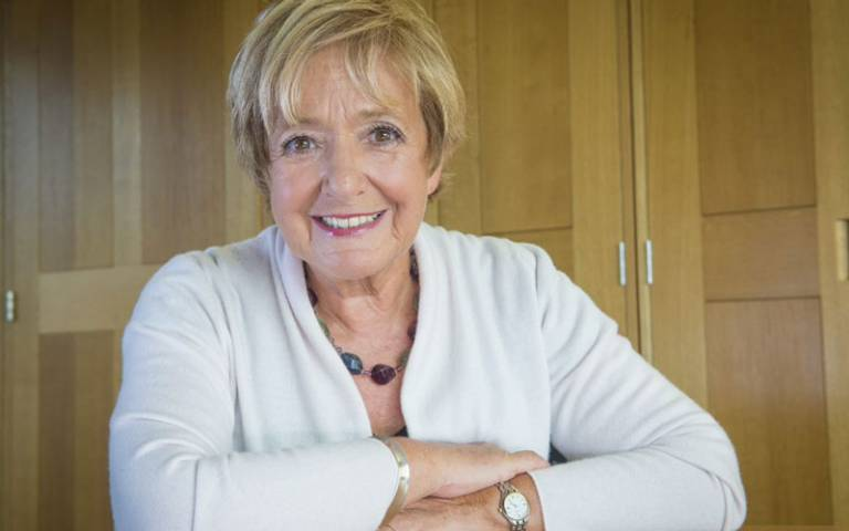 Dame Margaret Hodge. Smiling and wearing white top and sitting in a wood panelled room