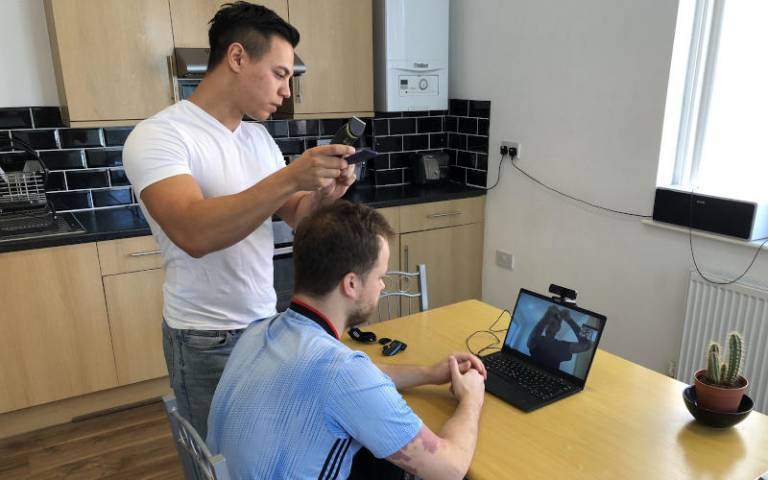 Image of someone getting their hair cut in front of a laptop