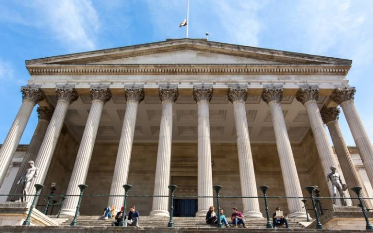 Students sitting in small groups on the steps outside the UCL Portico building