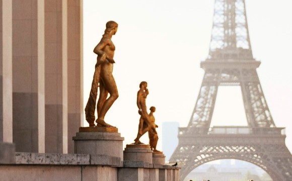 Three statues on top of a white building with the Eiffel Tower in the background